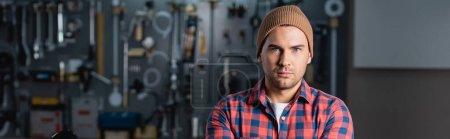 Photo pour Jeune réparateur en chemise à carreaux et bonnet regardant la caméra dans le garage, bannière - image libre de droit