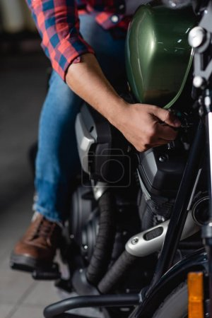 cropped view of mechanic making diagnostics of motorcycle in workshop, blurred background