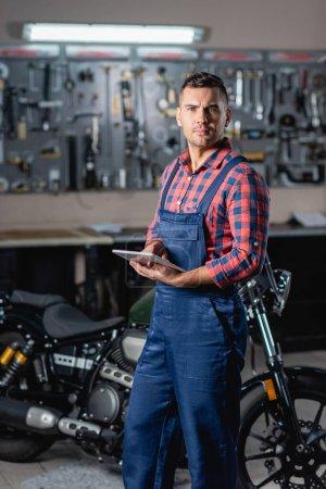 Photo pour Jeune technicien en salopette regardant la caméra tout en se tenant près de la moto avec tablette numérique, fond flou - image libre de droit