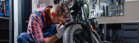 Foto de Joven mecánico en camisa a cuadros que comprueba rueda de la motocicleta en taller, bandera - Imagen libre de derechos