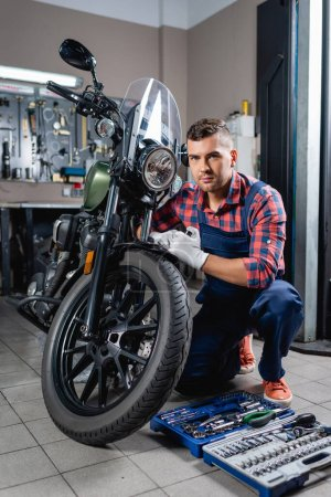 young technician in overalls looking at camera near motorcycle and toolbox in workshop