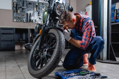 Photo for Young technician in overalls making diagnostics of motorcycle in garage near toolbox - Royalty Free Image
