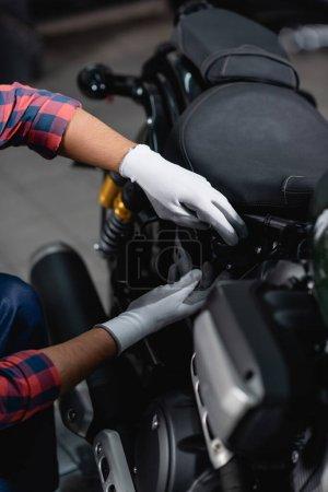 Ausgeschnittene Ansicht des Mechanikers in Handschuhen, die Diagnose des Motorrads in der Werkstatt stellt, verschwommener Vordergrund