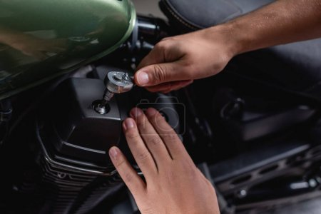 cropped view of mechanic using socket wrench while making diagnostics of motorcycle in workshop