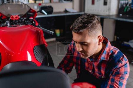 jeune mécanicien en chemise à carreaux examinant la moto en atelier, avant-plan flou