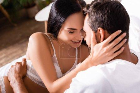 sensual brunette woman in lingerie hugging man indoors on blurred background