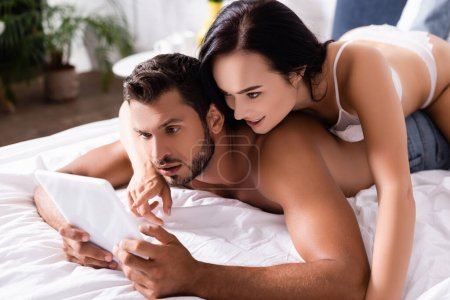 Photo for Smiling sexy woman pointing with finger at tablet while lying on surprised man in bedroom on blurred background - Royalty Free Image