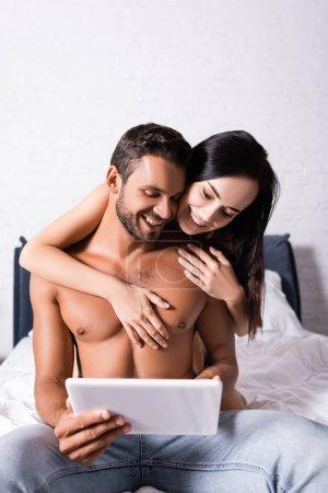 Foto de Sonriente morena mujer abrazando sin camisa hombre con tableta en la cama - Imagen libre de derechos
