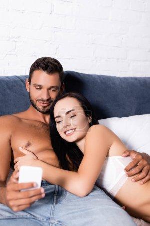 Photo pour Sourire jeune couple regardant smartphone tout en étant couché sur le lit - image libre de droit