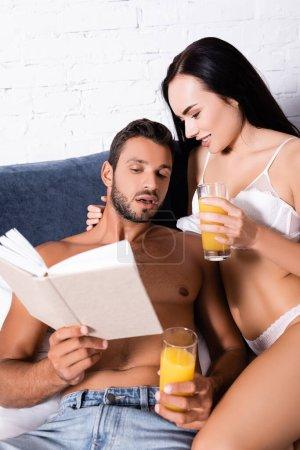 Photo pour Sexy jeune couple avec des verres de jus livre de lecture dans la chambre à coucher sur le premier plan flou - image libre de droit