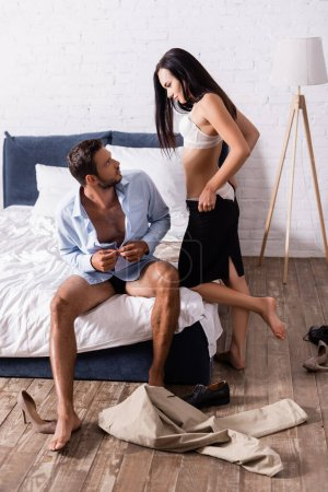Photo for Full length of young couple looking at each other while wearing in bedroom - Royalty Free Image