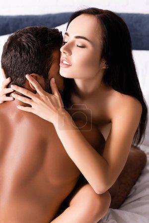 femme brune sensuelle avec les yeux fermés étreignant homme torse nu sur le lit