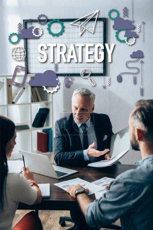 Photo pour Investisseur souriant pointant vers le dossier papier près de l'ordinateur portable et les gens d'affaires avec des documents sur l'avant-plan flou, lettrage de stratégie - image libre de droit