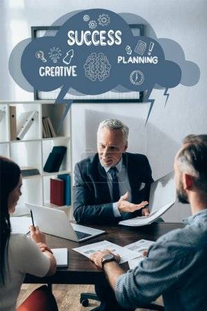 Investor in formal wear pointing at paper folder near laptop and business partners on blurred foreground, success, creative and planning illustration