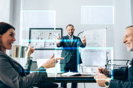 Cheerful investor pointing with fingers at smiling businesspeople on blurred foreground, illustration of screen with data