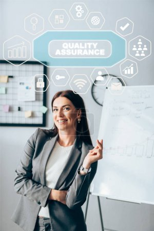 Positive investor looking at camera near symbols and quality assurance illustration on office