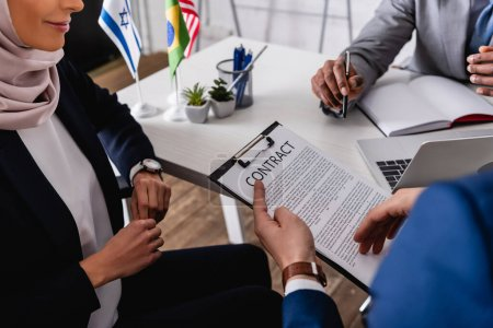 Photo for Cropped view of interpreter holding contract during meeting with multicultural business partners, blurred foreground - Royalty Free Image
