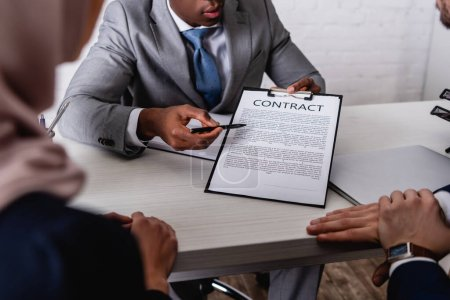 partial view of african american businessman pointing at contract during negotiation with interracial business partners, blurred foreground