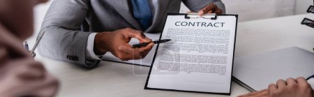 cropped view of african american businessman pointing with pen at contract near business partners on blurred foreground, banner