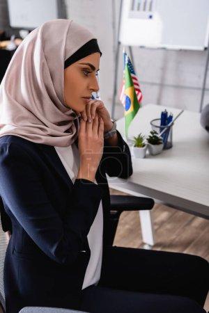 Photo pour Femme d'affaires arabe réfléchie dans le hijab assis au bureau près des drapeaux internationaux sur fond flou - image libre de droit
