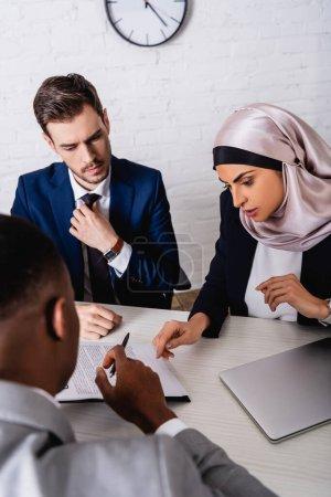 Photo pour Arabe femme d'affaires pointant du doigt le contrat lors d'une rencontre avec un partenaire afro-américain et interprète, avant-plan flou - image libre de droit