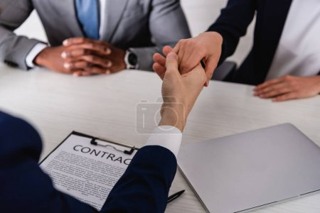 selective focus of business partners shaking hands near contract and african american businessman, cropped view
