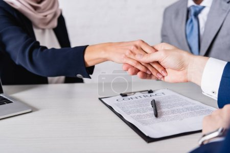 cropped view of business partners shaking hands near contract, blurred background