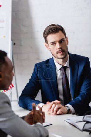 Photo for Serious european businessman looking at african american business partner on blurred foreground - Royalty Free Image