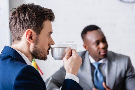Foto de Intérprete bebiendo café cerca de socio de negocios afroamericano sobre fondo borroso - Imagen libre de derechos