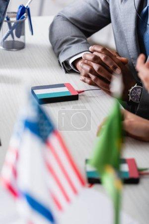 Photo pour Vue recadrée d'un homme d'affaires afro-américain assis les mains serrées près d'un traducteur numérique avec l'emblème du drapeau uae, au premier plan flou - image libre de droit