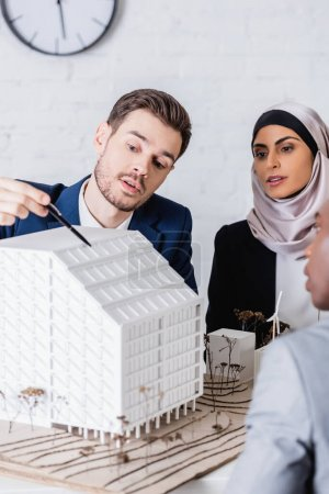 Photo pour Interprète pointant avec stylo au modèle de bâtiment à piles solaires près des partenaires arabo-afro-américains, au premier plan flou - image libre de droit
