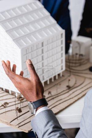 Photo pour Vue partielle de l'homme d'affaires afro-américain pointant avec la main au modèle de construction, arrière-plan flou - image libre de droit