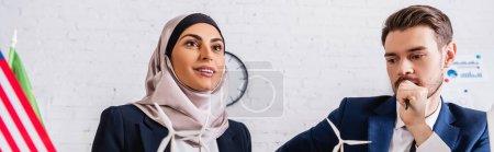 Photo pour Heureuse femme d'affaires arabe près des modèles d'éolienne et interprète, bannière - image libre de droit