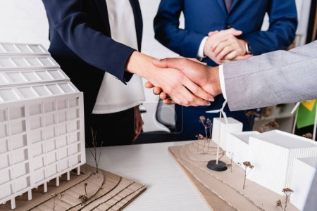 partial view of interracial business partners shaking hands near model of building with alternative power station