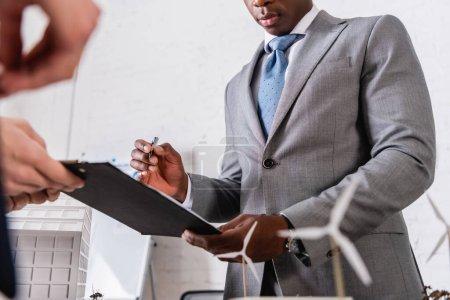Photo pour Vue partielle d'un homme d'affaires afro-américain tenant un stylo près du presse-papiers et d'un partenaire d'affaires au premier plan flou - image libre de droit