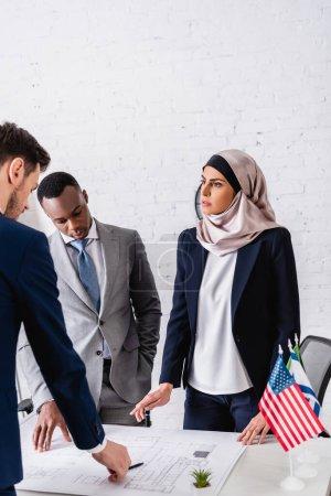Photo pour Femme d'affaires arabe sérieuse pointant du doigt près du plan directeur lors d'une réunion avec des partenaires d'affaires interracial - image libre de droit