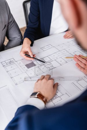 Photo for Cropped view of business partners pointing with pencil and pen at blueprint, blurred foreground - Royalty Free Image