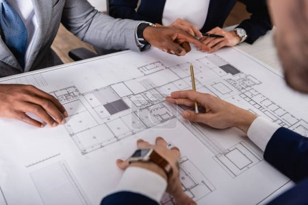 partial view of african american businessman pointing with finger at blueprint near multicultural partners, blurred foreground