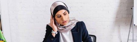 Photo pour Traducteur arabe dans casque sur hijab travaillant dans le bureau, bannière - image libre de droit