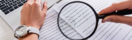cropped view of translator holding magnifying glass near documents with english text, banner