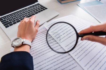 Photo pour Vue recadrée du traducteur tenant une loupe près des documents avec du texte anglais, premier plan flou - image libre de droit