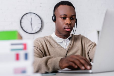 young african american translator in headset working at laptop on blurred foreground