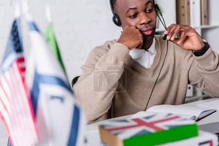 thoughtful african american translator in headset working near international flags and dictionaries on blurred foreground