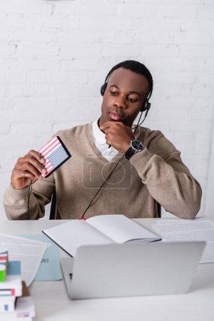 reflexivo intérprete afroamericano en auriculares con traductor digital con emblema de bandera de EE.UU. cerca de portátil y portátil en primer plano borroso