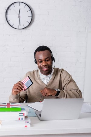 cheerful african american interpreter holding digital translator with usa flag emblem near laptop and dictionaries on blurred foreground
