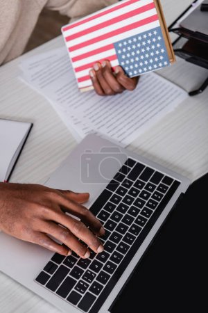 cropped view of african american translator typing on laptop while holding dictionary with usa flag on cover