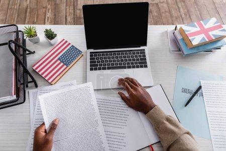 vista parcial del traductor afroamericano que trabaja con documentos cerca de la computadora portátil y diccionarios con EE.UU. y grandes banderas británicas en portadas