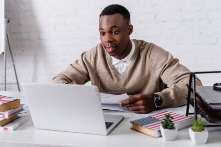 Photo for Amazed african american translator working at laptop near dictionaries on blurred foreground - Royalty Free Image