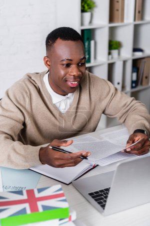 smiling african american translator working with documents near laptop and dictionaries on blurred foreground