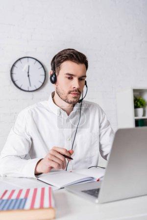 Junge Übersetzerin im Headset mit Stift in der Nähe von Notizbuch und Wörterbuch auf verschwommenem Vordergrund
